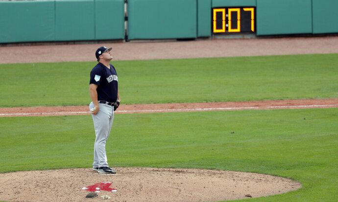 New York Yankees pitcher Cale Coshow prepares to pitch as the pitching clock winds down during a spring training baseball game against the Boston Red Sox in Fort Myers, Fla., Saturday, Feb. 23, 2019. (AP Photo/Gerald Herbert)