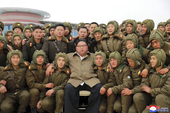 "In this undated photo provided on Monday, Nov. 18, 2019, by the North Korean government, North Korean leader Kim Jong Un, center, poses with North Korean air force sharpshooters and soldiers for a photo at an unknown location in North Korea. Kim supervised a parachuting drill of military sharpshooters and vowed to build an ""invincible army,"" displaying more defiance even as the United States and South Korea called off their own exercises to create space for nuclear diplomacy. Independent journalists were not given access to cover the event depicted in this image distributed by the North Korean government. The content of this image is as provided and cannot be independently verified. Korean language watermark on image as provided by source reads:"
