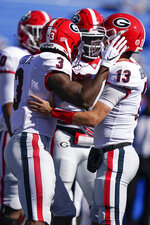 Georgia quarterback Stetson Bennett (13) celebrates with teammates after scoring a touchdown during the first half of an NCAA college football game, Oct. 31, 2020, in Lexington, Ky. (AP Photo/Bryan Woolston)