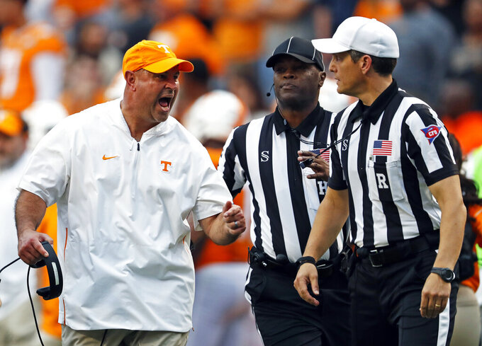 Tennessee head coach Jeremy Pruitt yells at referee Steve Marlow, right, after a call as head linesman Ralph Green follows in the first half of an NCAA college football game against South Carolina, Saturday, Oct. 26, 2019, in Knoxville, Tenn. (AP Photo/Wade Payne)