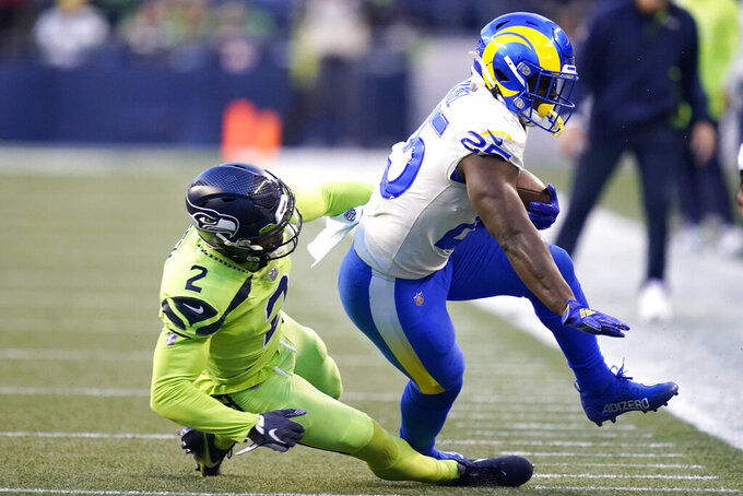 Los Angeles Rams running back Sony Michel (25), right, is tackled by Seattle Seahawks free safety D.J. Reed (2) during the first half of an NFL football game, Thursday, Oct. 7, 2021, in Seattle. (AP Photo/Elaine Thompson)