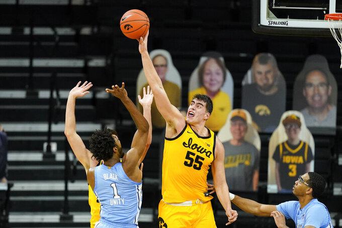Iowa center Luka Garza (55) blocks a shot by North Carolina guard Leaky Black (1) during the second half of an NCAA college basketball game, Tuesday, Dec. 8, 2020, in Iowa City, Iowa. Iowa won 93-80. (AP Photo/Charlie Neibergall)
