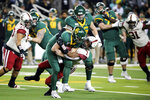 Baylor quarterback Charlie Brewer, left center, is sacked by Oklahoma defensive lineman Ronnie Perkins, right center, during the second half of an NCAA college football game in Waco, Texas, Saturday, Nov. 16, 2019. Oklahoma won 34-31. (AP Photo/Ray Carlin)