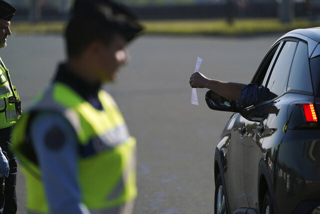 Police officers check documents to ensure nationwide confinement measures due to coronavirus are upheld, at a highway toll gate in Villefranche our Saone, north of Lyon, central France, Friday, April 3, 2020. Friday marks the first day of springtime school holidays for a large part of France including Paris, when under normal circumstances cars would clog highways as families head on vacation around the country. The new coronavirus causes mild or moderate symptoms for most people, but for some, especially older adults and people with existing health problems, it can cause more severe illness or death. (AP Photo/Laurent Cipriani)