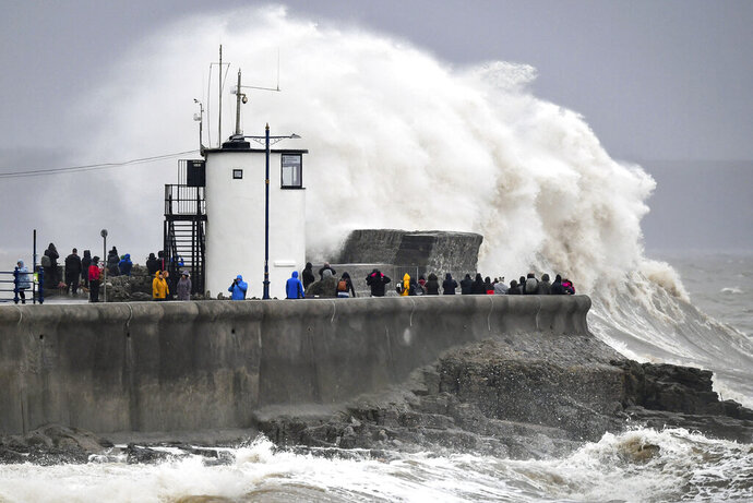 People watch waves and rough seas pound against the harbour wall at Porthcawl in Wales, as Storm Dennis sweeps across the country, Saturday Feb. 15, 2020.  Enormous waves  are churning across the North Atlantic as Britain braces for a second straight weekend of wild winter weather and flooding. (Ben Birchall/PA via AP)