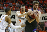 Kansas State forward Dean Wade, right, grabs a rebound in front of Oklahoma State guard Curtis Jones (1) and guard Thomas Dziagwa (4) during the first half of an NCAA college basketball game in Stillwater, Okla., Saturday, Feb. 2, 2019. (AP Photo/Sue Ogrocki)