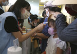 A young participant has her temperature checked before a mock trip abroad at Taipei Songshan Airport in Taipei, Taiwan, Tuesday, July 7, 2020. Dozens of would-be travelers acted as passengers in an activity organized by Taiwan's Civil Aviation Administration to raise awareness of procedures to follow when passing through customs and boarding their plane at Taipei International Airport. (AP Photo/Chiang Ying-ying)