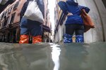 People wade their way through water in Venice, Italy, Friday, Nov. 15, 2019. Exceptionally high tidal waters returned to Venice on Friday, prompting the mayor to close the iconic St. Mark's Square and call for donations to repair the Italian lagoon city just three days after it experienced its worst flooding in 50 years. (AP Photo/Luca Bruno)