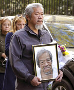 REMOVES REFERENCE TO HOMELESS KILLED  -  A mourner carries a photo of Chuen Kok after his funeral at the Ng Fook Funeral Home Friday Oct. 18, 2019, in New York.  Kok, an 83-year-old homeless man whom Chinatown residents warmly greeted as
