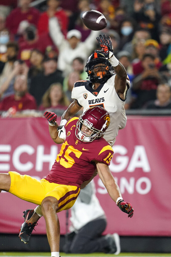 Oregon State defensive back Alex Austin, top, is called for pass interference while defending against Southern California wide receiver Drake London during the first half of an NCAA college football game Saturday, Sept. 25, 2021, in Los Angeles. (AP Photo/Marcio Jose Sanchez)