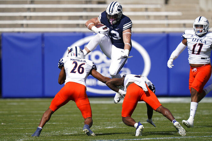 BYU tight end Masen Wake (13) hurdles UTSA's Corey Mayfield Jr. (26) and Antonio Parks in the first half during an NCAA college football game Saturday, Oct. 10, 2020, in Provo, Utah. (AP Photo/Rick Bowmer, Pool)