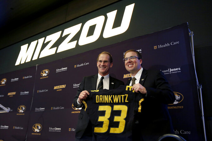 University of Missouri Director of Athletics Jim Sterk, left, holds up a jersey with Eliah Drinkwitz after introducing Drinkwitz as the new NCAA college football head coach at the school, Tuesday, Dec. 10, 2019, in Columbia, Mo. Drinkwitz becomes the 33rd head football coach at Missouri after coaching the 2019 season at Appalachian State. (AP Photo/Jeff Roberson)