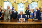 FILE - In this Friday, July 19, 2019, file photo, President Donald Trump, center, listens to Apollo 11 astronaut Michael Collins, left, accompanied by Buzz Aldrin, Vice President Mike Pence and first lady Melania Trump, during a photo opportunity commemorating the 50th anniversary of the Apollo 11 moon landing, in the Oval Office of the White House in Washington. Collins, who circled the moon in the mother ship while Aldrin and Neil Armstrong planted a U.S. flag and gathered rocks, acknowledges that returning to the moon as a precursor to Mars is