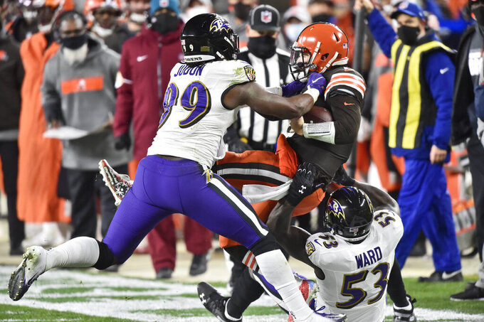Cleveland Browns quarterback Baker Mayfield, center, is tackled by Baltimore Ravens outside linebacker Matt Judon (99) and defensive end Jihad Ward (53) during the first half of an NFL football game, Monday, Dec. 14, 2020, in Cleveland. (AP Photo/David Richard)