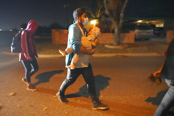 A migrant carries a child as their group follows an official to an intake area after turning themselves in upon crossing the U.S.-Mexico border, early Wednesday, March 24, 2021, in Roma, Texas. A surge of migrants on the Southwest border has the Biden administration on the defensive. The head of Homeland Security acknowledged the severity of the problem but insisted it's under control and said he won't revive a Trump-era practice of immediately expelling teens and children. (AP Photo/Julio Cortez)