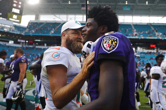 Miami Dolphins quarterback Ryan Fitzpatrick (14) congratulates Baltimore Ravens quarterback Lamar Jackson (8), at the end of an NFL football game, Sunday, Sept. 8, 2019, in Miami Gardens, Fla. The Ravens defeated the Dolphins 59-10. (AP Photo/Brynn Anderson)