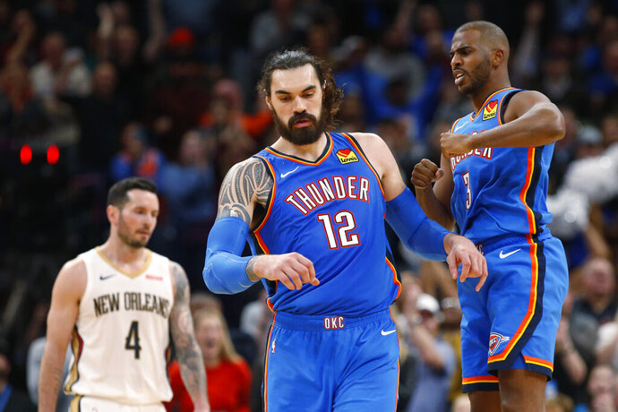 Oklahoma City Thunder center Steven Adams (12) celebrates with teammate Chris Paul (3) in front of New Orleans Pelicans guard J.J. Redick (4) late in the second half of an NBA basketball game Friday, Nov. 29, 2019, in Oklahoma City. (AP Photo/Sue Ogrocki)