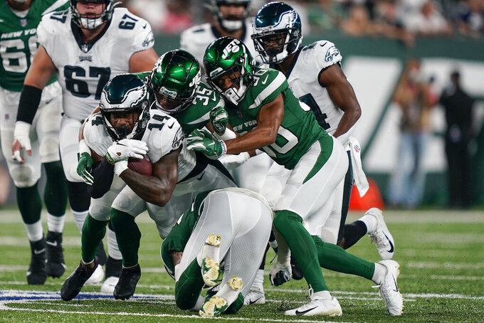New York Jets' Sharrod Neasman (35) and Michael Carter II (30) tackle Philadelphia Eagles' Kenneth Gainwell (14) during the first half of an NFL preseason football game Friday, Aug. 27, 2021, in East Rutherford, N.J. (AP Photo/John Minchillo)