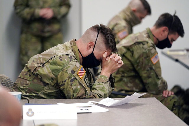 Minnesota National Guard chaplains bow during a prayer after a time of devotion Oct. 19, 2020 in St. Paul, Minn. The role of faith leaders who serve as National Guard chaplains has grown more crucial, and more challenging, as thousands of soldiers and airmen, most of them in their 20s, have been increasingly deployed not only in long-lasting overseas wars but in civil unrest across a deeply polarized United States, including the civil unrest following the death of George Floyd at the hands of Minneapolis police. (AP Photo/Jim Mone)