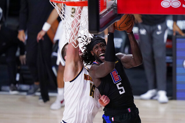 FILE - In this Sept. 15, 2020, file photo, Los Angeles Clippers forward Montrezl Harrell (5) drives to the basket Denver Nuggets center Nikola Jokic (15) during the second half of an NBA conference semifinal playoff basketball game in Lake Buena Vista, Fla. Harrell says he decided to move from the Clippers to the crosstown rival Los Angeles Lakers as a free agent partly because the champion Lakers pursued him much more aggressively. (AP Photo/Mark J. Terrill, File)