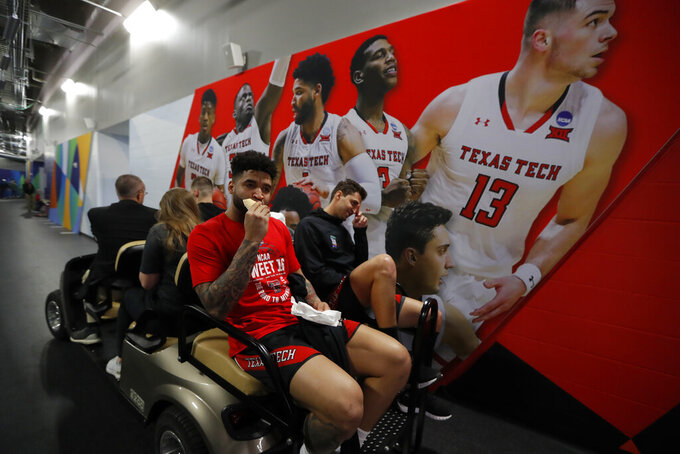 Texas Tech's Brandone Francis, left, and Davide Moretti ride on the back of the cart during a news conference for the championship of the Final Four NCAA college basketball tournament, Sunday, April 7, 2019, in Minneapolis. Texas Tech will play Virginia on Monday for the national championship. (AP Photo/Charlie Neibergall)