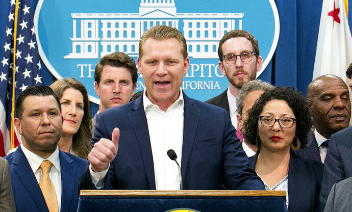 FILE - In this Monday, July 17, 2017 file photo, Assembly Republican Leader Chad Mayes, R-Yucca Valley, center, discusses the cap-and-trade bill at the Capitol in Sacramento, Calif. The super-minority in the Legislature has lost another state lawmaker, as former Assembly Republican leader Chad Mayes of Yucca Valley has decided to run for re-election in 2020 with no party preference.(AP Photo/Rich Pedroncelli, File)