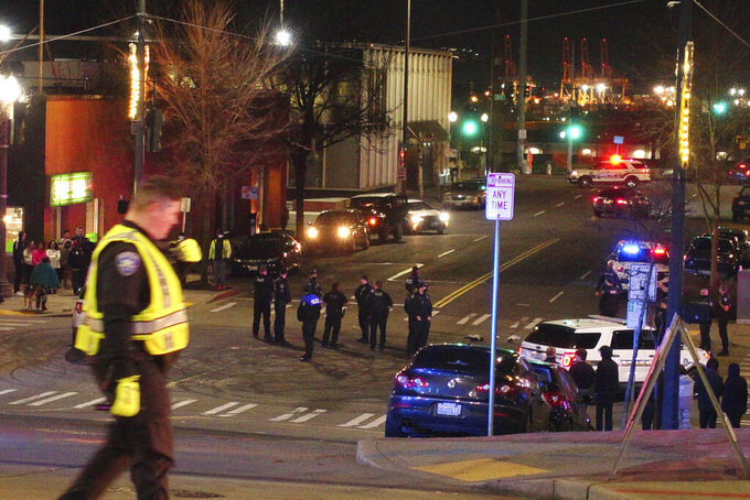 Tacoma Police and other law enforcement vehicles are shown near the site of a car crash Saturday, Jan. 23, 2021, in downtown Tacoma, Wash. At least one person was injured when a police car plowed through a crowd of people Saturday night who were watching a downtown street race, the Tacoma News-Tribune reported. (AP Photo/Ted S. Warren)