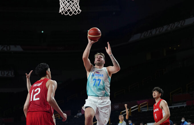 Slovenia's Luka Doncic (77) drives to the against Japan's Yuta Watanabe (12), left, during men's basketball preliminary round game at the 2020 Summer Olympics, Thursday, July 29, 2021, in Saitama, Japan. (AP Photo/Eric Gay)