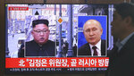 A man passes by a TV screen showing images of North Korean leader Kim Jong Un, left, and Russian President Vladimir Putin, right, during a news program at the Seoul Railway Station in Seoul, South Korea, Tuesday, April 23, 2019. North Korea confirmed Tuesday that Kim will soon visit Russia to meet with Putin in a summit that comes at a crucial moment for tenuous diplomacy meant to rid the North of its nuclear arsenal. The screen reads: