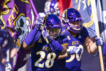 East Carolina defensive back Ahonore Varner (28) carries out the team flag before an NCAA football game against Navy on Saturday, Oct. 17, 2020, in Greenville, N.C. (AP Photo/Jacob Kupferman)