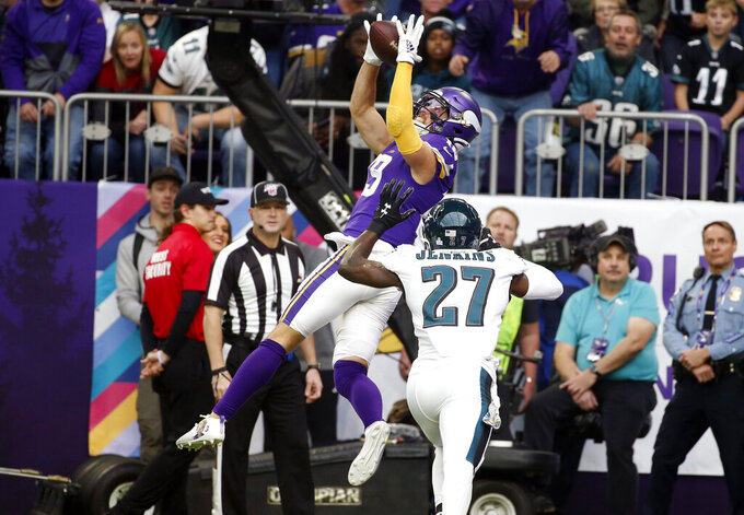 FILE - In this Sunday, Oct. 13, 2019 file photo, Minnesota Vikings wide receiver Adam Thielen, left, tries to catch a pass over Philadelphia Eagles strong safety Malcolm Jenkins (27) during the first half of an NFL football game in Minneapolis. Adam Thielen's season has been hamstrung by a hamstring injury, but the two-time Pro Bowl wide receiver remains an integral part of the offense for the Minnesota Vikings as evidenced by his diving catch in overtime to set up the playoff game win at New Orleans. (AP Photo/Bruce Kluckhohn, File)