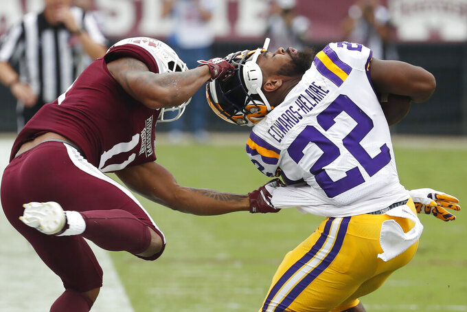 Mississippi State safety Jaquarius Landrews (11) pulls the helmet off LSU running back Clyde Edwards-Helaire (22) during the first half of their NCAA college football game in Starkville, Miss., Saturday, Oct. 19, 2019. Landrews was flagged for a personal foul. (AP Photo/Rogelio V. Solis)