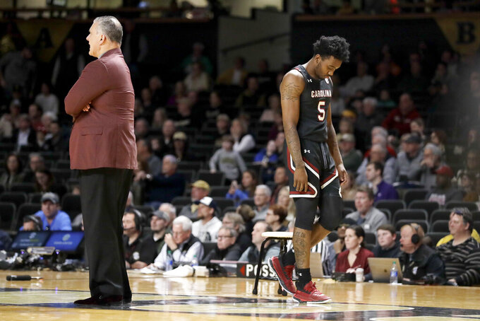 South Carolina guard Jermaine Couisnard (5) walks past head coach Frank Martin after fouling out in the second half of an NCAA college basketball game against Vanderbilt Saturday, March 7, 2020, in Nashville, Tenn. Vanderbilt won 83-74. (AP Photo/Mark Humphrey)