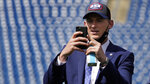 New England Patriots 2021 first-round draft pick, former Alabama quarterback Mac Jones snaps a photograph of the football field, Friday, April 30, 2021, in Foxborough, Mass. The Patriots selected Jones with the 15th pick in Thursday's NFL Draft. (AP Photo/Charles Krupa)
