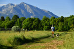 With Mount Sopris in the background Alex Eherenman walks his dog Nina in a local dog park before heading to work on July 1, 2021 in Carbondale, Colo.    Eherenman has lived in his truck-bed camper on and off since 2017 trying to make enough at his jobs while trying to save money so he can afford either a security deposit for an apartment or the down payment on an apartment come winter time.  (Helen H. Richardson /The Denver Post via AP)