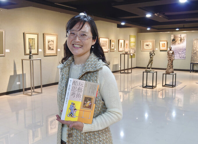"""In this photo taken on March 23, 2021, Taiwanese author Iris Chiang holds her book """"Play with Art"""" at the saloon featuring Taiwanese artist YUYU Yang's work in Taipei, Taiwan. Four years on after being sold to a Chinese publisher and no going to press, Chiang's book that teaches children how to appreciate art has fallen victim to the heightened tensions between China and Taiwan that are spilling over into the cultural sphere. (AP Photo/Chiang Ying-ying)"""