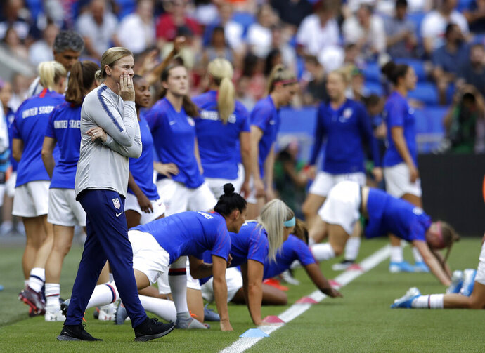 FILE - In this July 7, 2019, file photo, U.S. coach Jill Ellis watches her players warm up for the tema's Women's World Cup soccer final against the Netherlands in Decines, outside Lyon, France.  Ellis likened her tenure in charge the U.S. women's national team to an amusement park ride. Later, she compared it to a tumultuous ride on a five-year wave. The most successful coach in program history seems quite content to get off this merry-go-round on her own terms. (AP Photo/Alessandra Tarantino, File)