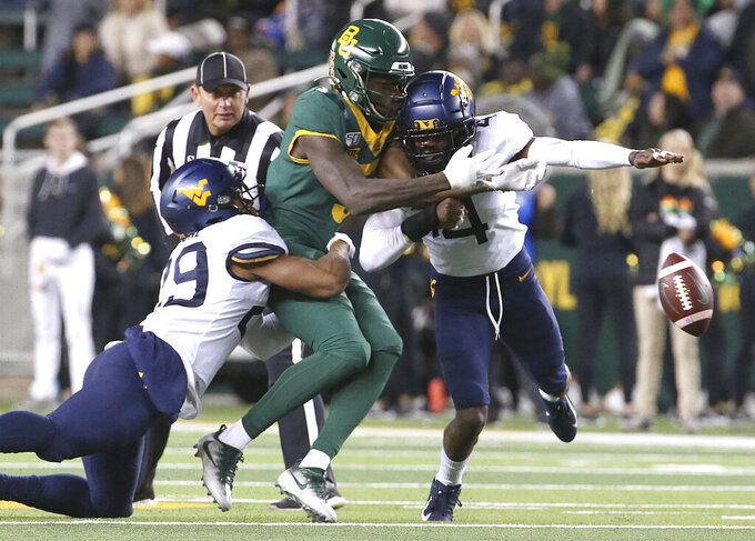 FILE - In this Oct. 31, 2019, file photo, Baylor wide receiver Denzel Mims (5) is hit West Virginia safety Josh Norwood (4) and safety Sean Mahone (29) during the first half of an NCAA college football game in Waco, Texas. Norwood was then ejected for targeting. Players ejected from football games for targeting will be allowed to remain on the sidelines, the NCAA announced Tuesday, April 21, 2020. (AP Photo/Jerry Larson, File)