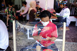A man checks his mobile phone at a coffee shop, sitting in front of a plastic sheet barrier installed to help curb the new coronavirus outbreak in Makassar, South Sulawesi, Indonesia, Sunday, May 31, 2020. (AP Photo/Masyudi S. Firmansyah)