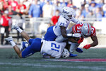 Ohio State running back Master Teague, right, is tackled by Tulsa defensive backs Bryson Powers, bottom, and Jaise Oliver during the first half of an NCAA college football game Saturday, Sept. 18, 2021, in Columbus, Ohio. (AP Photo/Jay LaPrete)