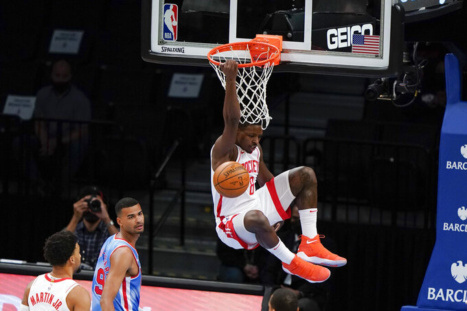 Houston Rockets' Jae'Sean Tate (8) dunks in front of Brooklyn Nets' Timothe Luwawu-Cabarrot (9) during the first half of an NBA basketball game Wednesday, March 31, 2021, in New York. (AP Photo/Frank Franklin II)