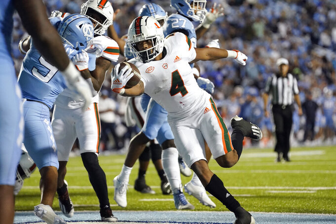 Miami running back Jaylan Knighton (4) scores a touchdown against North Carolina during the second half of an NCAA college football game in Chapel Hill, N.C., Saturday, Oct. 16, 2021. (AP Photo/Gerry Broome)