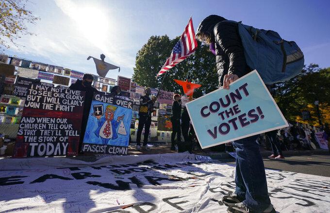 A demonstrator reads a banner on display at Black Lives Matter Plaza, Thursday, Nov. 5, 2020, in Washington. (AP Photo/Alex Brandon)