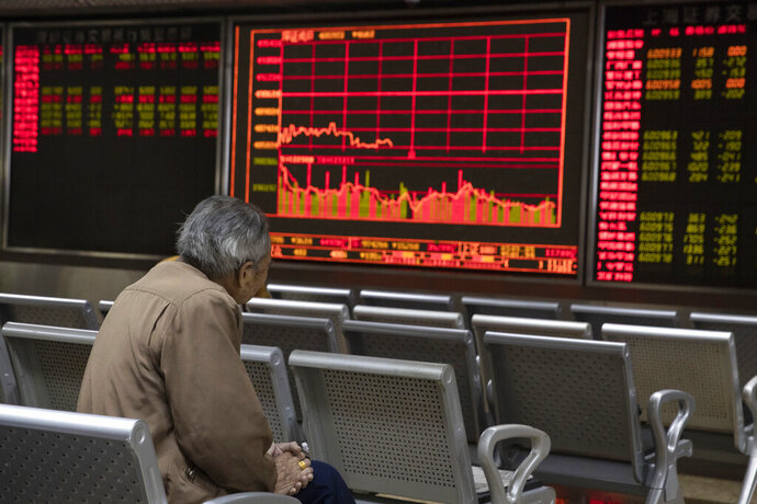 In this Nov. 11, 2019, photo, an investor monitors stock prices at a brokerage in Beijing. Shares were mixed in Asia on Tuesday, Nov. 12, as investors awaited cues on trade talks between China and the U.S.  (AP Photo/Ng Han Guan)