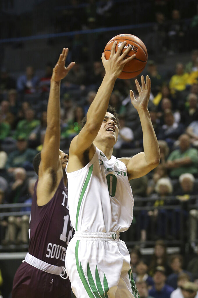 Oregon's Will Richardson, right, goes up for a shot ahead of Texas Southern's John Jones during the first half of an NCAA college basketball game in Eugene, Ore., Saturday, Dec. 21, 2019. (AP Photo/Chris Pietsch)