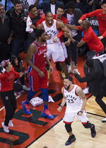 FILE- In this May 12, 2019, file photo, Toronto Raptors forward Kawhi Leonard (2) reacts with teammates after making the game-winning shot at the buzzer to defeat the Philadelphia 76ers in an NBA Eastern Conference semifinal basketball game in Toronto. (Nathan Denette/The Canadian Press via AP, File)