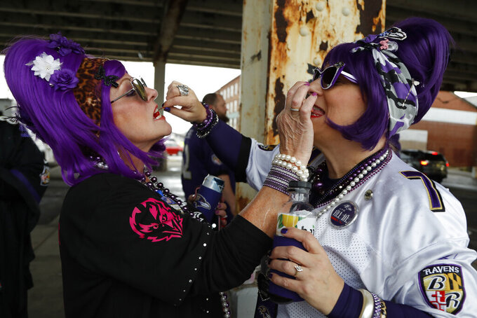 Baltimore Ravens fans speak ahead of the first half of an NFL divisional playoff football game between the Baltimore Ravens and the Tennessee Titans, Saturday, Jan. 11, 2020, in Baltimore. (AP Photo/Julio Cortez)