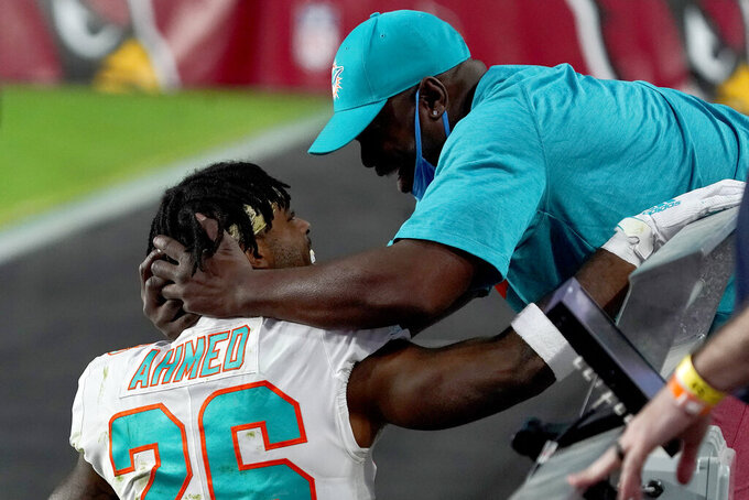 Miami Dolphins running back Salvon Ahmed hugs his dad, Randy Ahmed after an NFL football game against the Arizona Cardinals, Sunday, Nov. 8, 2020, in Glendale, Ariz. The Dolphins won 34-31. (AP Photo/Rick Scuteri)