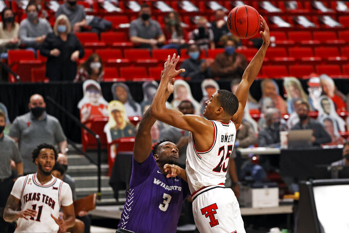Texas Tech's Nimari Burnett (25) tries to dunk over Abilene Christian's Airion Simmons (3) during the second half of an NCAA college basketball game Wednesday, Dec. 9, 2020, in Lubbock, Texas. (AP Photo/Brad Tollefson)