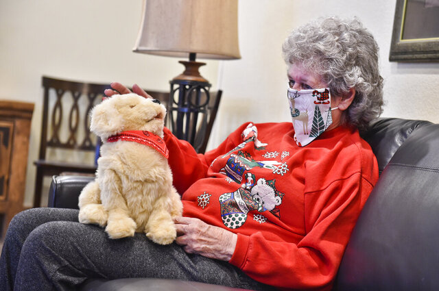 Margie Copenhaver, an 83-year-old resident of Eagle Manor in Helena, Mont., pets her robotic pet dog Muffie, Dec. 11, 2020.